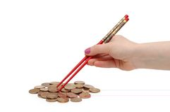 Hand with red chopsticks. Eating golden coins Stock Image