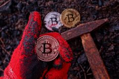 A hand with a gesture of approval and a coin bitcoin over the ground with a hammer. A hand in a red glove with a gesture of approval and a coin bitcoin over the Stock Image