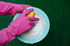 The hand in a red glove washes the washcloth with a dish stock photos