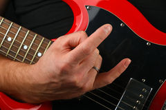 Hand with red guitar and devil horns  on black. Male hand holding red sg guitar body under neck with devil horns rock metal sign  on black background Stock Photo