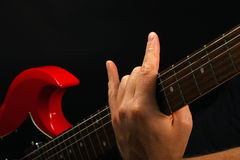 Hand with red guitar and devil horns  on black Royalty Free Stock Photos