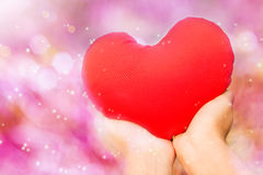 Hand and red heart in dreamy sweet and romantic pink bokeh Stock Images