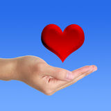 Hand with Red Heart. Hand underneath illustration of red heart with blue background royalty free stock photos