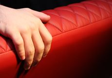 Hand on red leather sofa Stock Photo