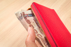 Hand and red leather wallet with thai banknote money, close up Royalty Free Stock Photos