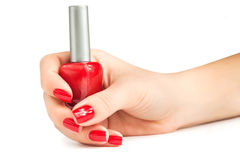 Hand with red nail polish bottle isolated Royalty Free Stock Images