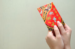 Hand with red packet. Handing over a red packet with space at the other side for text Stock Image