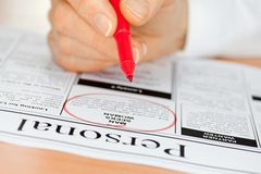 Hand with Red Pen Checking Personals in Newspaper Stock Images
