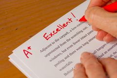 Hand with Red Pen Grading Papers with Excellent Royalty Free Stock Photography