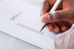 Hand with red pen marking a check box Stock Image