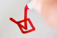 Hand with red pen marking a check box Royalty Free Stock Photos
