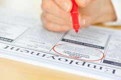 Hand with Red Pen Marking Job in Newspaper Royalty Free Stock Photography