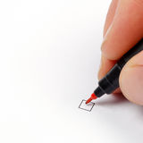 Hand with red pen ready to mark a checkbox Stock Image