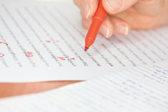 Hand with Red Pen Transcribing a Story Stock Images