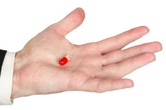 Hand with red pill, white background Stock Photos