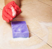 Hand in red rubber glove clean a house floor Stock Photo