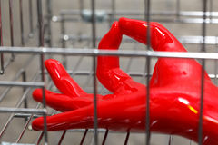 Hand in red rubber glove inside chrome cage Stock Photos