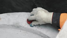 Hand in red rubber glove scew plastic plug in piece of concrete in ditch stock footage