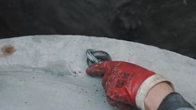 Hand in red rubber glove unscew metal noose from piece of concrete in ditch stock footage