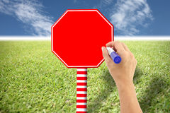 Hand and red sign on the lawn and blue sky. Royalty Free Stock Photography