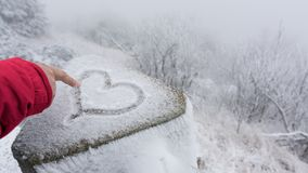 Female finger draws a symbolic heart for good luck in the snow. Hand in red sleeve and symbol of love with frosty winter landscape in background royalty free stock photography