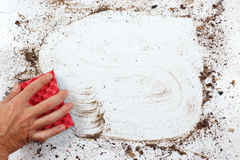 Hand with red sponge wiping very dirty surface Royalty Free Stock Image