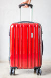 Hand on red travelling suitcase Royalty Free Stock Photography
