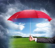 Hand with an red umbrella. Businessman hand with an red umbrella with sunny nature view Stock Images