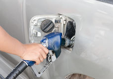 Hand refilling the car with fuel. Royalty Free Stock Images