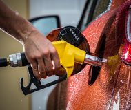 Hand refilling the car with fuel. Stock Photo