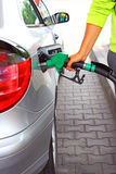Hand refilling the car with fuel on a filling station Stock Photo