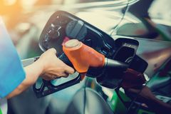Hand refilling the car with fuel stock image