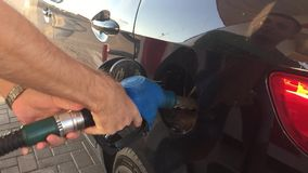 Hand refilling the car with fuel. Refuel station. Car refueling on petrol station. Man pumping gasoline oil.