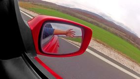 Hand reflection view in a rear view mirror of a fast sport car.