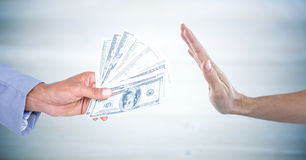 Hand refusing money against blurry grey wood panel Royalty Free Stock Images