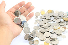Hand releasing coins over white Royalty Free Stock Photography