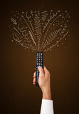 Hand with remote control and curly lines Royalty Free Stock Photos