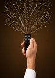 Hand with remote control and curly lines Stock Image