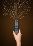 Hand with remote control and curly lines Stock Images