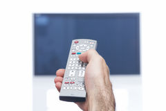 Hand with remote control and flat tv Royalty Free Stock Image
