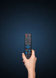 Hand with remote control. Hand holding a remote control on blue background Stock Photos