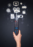 Hand with remote control and media icons Stock Photo