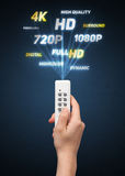 Hand with remote control and multimedia properties Royalty Free Stock Photo