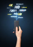 Hand with remote control and multimedia properties Royalty Free Stock Image