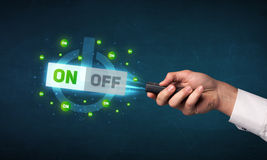 Hand with remote control and on-off signals Stock Image