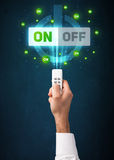 Hand with remote control and on-off signals Stock Photography
