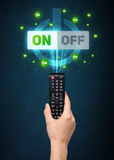 Hand with remote control and on-off signals Royalty Free Stock Images