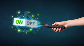 Hand with remote control and on-off signals Royalty Free Stock Image