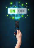Hand with remote control and on-off signals Royalty Free Stock Photo
