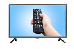 Hand with remote control pointing at modern TV set Stock Photo